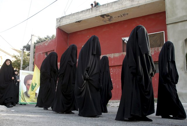 Muslim Shi'ite women carry a Hezbollah flag as they take part in a march organised by Hezbollah during a re-enactment of the battle of Kerbala during a mourning process, ahead of the day of Ashura, in Saksakieh village, southern Lebanon, October 18, 2015. (Photo by Ali Hashisho/Reuters)