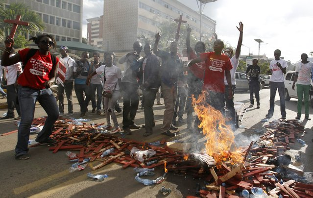 Protesters celebrate as they set ablaze wooden crosses, symbolising people killed in a series of attacks, during the #OccupyHarambeeAve demonstration in Kenya's capital Nairobi November 25, 2014. (Photo by Thomas Mukoya/Reuters)