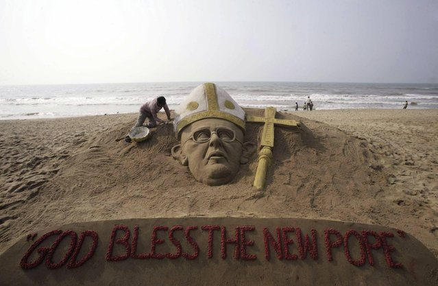 An Indian sand artist applies the finishing touches to a sand sculpture of the new pope at the Golden Sea beach on the Bay of Bengal coast in Puri, Orissa state, India, Thursday, March 14, 2013. Jorge Bergoglio of Argentina was elected pope Wednesday, becoming the first pontiff from the Americas and the first from outside Europe in more than a millennium. He chose the name Francis, associating himself with the humble 13th-century Italian preacher who lived a life of poverty.  (Photo by Biswaranjan Rout/AP Photo)
