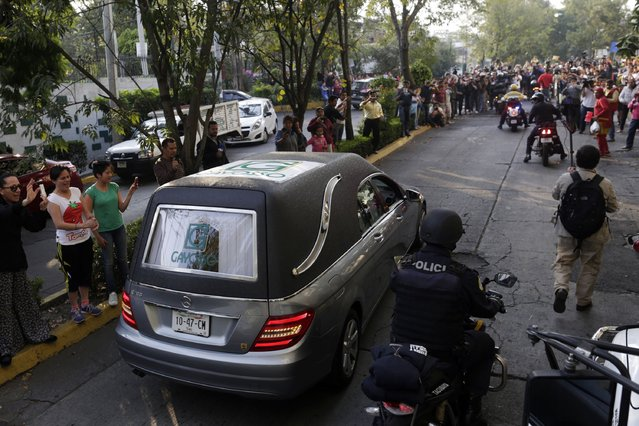 A funeral van with the body of Mexican actor and screenwriter Roberto Gomez Bolanos arrives at Mexican media company Televisa in Mexico City November 29, 2014. (Photo by Carlos Jasso/Reuters)