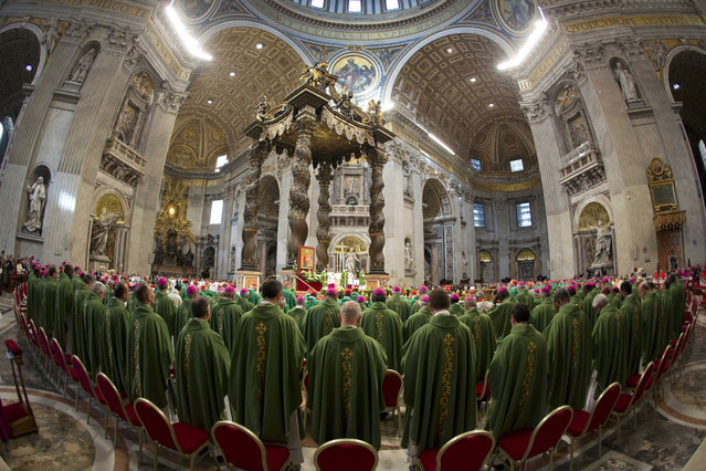 In this photo taken with a fish-eye lens Pope Francis celebrates a Mass to mark the end of the Synod of bishops, in St. Peter's Basilica at the Vatican, Sunday, October 25, 2015. Catholic bishops called for a more welcoming church for cohabitating couples, gays and Catholics who have divorced and civilly remarried, endorsing Pope Francis' call for a more merciful and less judgmental church. (Photo by Alessandra Tarantino/AP Photo)