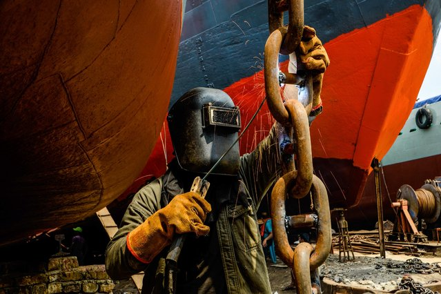 A laborer working at a shipyard near the Buriganga River on September 2, 2020. The shipbuilding industry in Bangladesh is spreading rapidly where workers from all ages work together. The working condition is not suitable for anyone as it is hot and often very dangerous, even workers do not use minimum safety guards and this often leads to accidents. (Photo by Piyas Biswas/SOPA Images/Rex Features/Shutterstock)