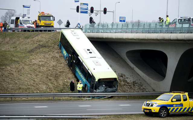 A bus of the public transport operator Connexxion sits on the embankment after an accident with a car on the provincial road N242 in Alkmaar, The Netherlands, on March 20, 2013. After the accident, the N242 was partially closed. (Photo by Olaf Kraak/AFP Photo)