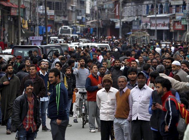 People stand on a road after vacating buildings following an earthquake in Srinagar October 26, 2015. (Photo by Danish Ismail/Reuters)