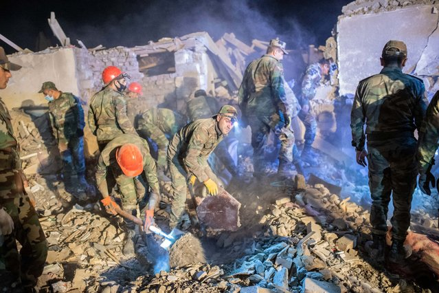 Rescue teams sift through rubble at a site hit by a missile strike during fighting over the breakaway region of Nagorno-Karabakh, in the city of Ganja, Azerbaijan early on October 17, 2020. A missile strike levelled several homes in Azerbaijan's second city of Ganja on October 17, with one resident telling AFP he saw seven victims pulled out of the rubble. (Photo by Bulent Kilic/AFP Photo)