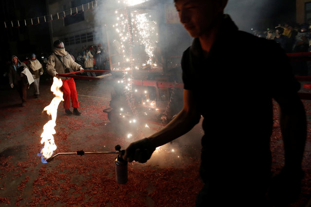 "A participant lights firecrackers during the ""Beehive Firecrackers"" festival at the Yanshui district in Tainan, Taiwan on March 1, 2018. (Photo by Tyrone Siu/Reuters)"