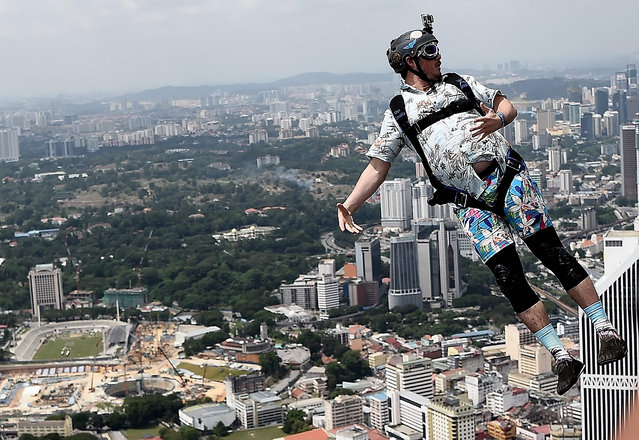 Base jumpers leap from the 300-metre high skydeck of Malaysia's landmark Kuala Lumpur Tower against the backdrop of the city's skyline on October 3, 2016 during the annual International KL Tower Base-Jump event. (Photo by Manan Vatsyayana/AFP Photo)
