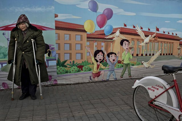 A disabled Chinese pensioner stands in the street next to a propaganda billboard showing a cartoon scene depicting the Great Hall of the People, in the street on December 1, 2014 in Beijing, China. Though China's economy is one of the fastest growing in the world and the standard of living has dramatically risen for millions in recent years, there are still many urban poor in the cities who are often migrants from rural areas. (Photo by Kevin Frayer/Getty Images)