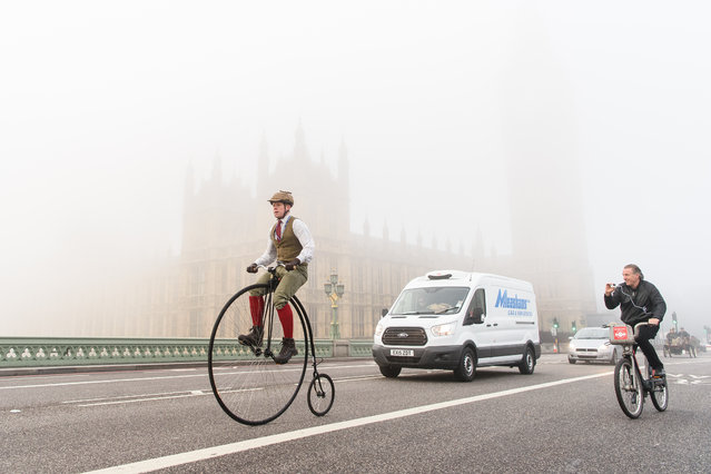 """A man rides a Penny Farthing bicycle past the Houses of Parliament in Westminster shortly after beginning the 119th """"Veteran Car Run"""" from Hyde Park in London, to Brighton in southern England, on November 1, 2015. Around 500 classic cars took part in the 60 mile journey to the south coast resort. (Photo by Leon Neal/AFP Photo)"""