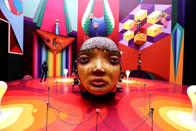 """A visitor looks at an artwork that forms part of the OsGemeos exhibition, titled """"Secretos (Secrets)"""", in Sao Paulo, Brazil, 15 October 2020. The OsGemeos exhibit marks the return of cultural life in Sao Paulo after seven months of inactivity due to the coronavirus pandemic. The show presents personal items and artworks of the Brazilian twin street artists Otavio and Gustavo Pandolfo, aka OsGemeos, in the centenary building of the Pinacoteca de Sao Paulo. (Photo by Sebastiao Moreira/EPA/EFE)"""