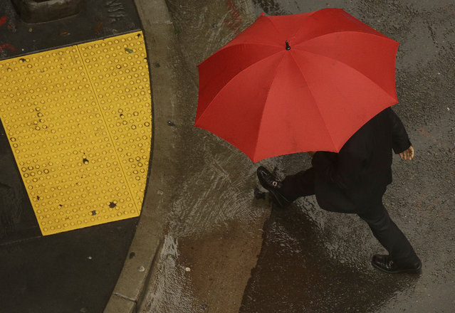 A man carries an umbrella as he crosses Montgomery Street in San Francisco, Thursday, December 4, 2014. The San Francisco Bay Area reached or exceeded normal annual rainfall totals for the first time in years. (Photo by Jeff Chiu/AP Photo)