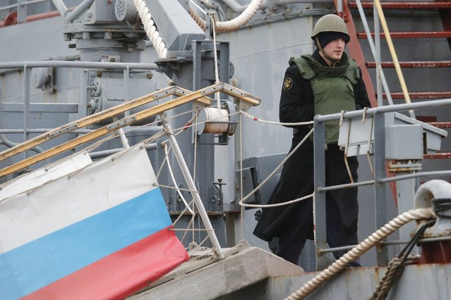 A Russian sailor stands on the deck of the Russian navy frigate Smolny at the STX Les Chantiers de l'Atlantique shipyard site in Saint-Nazaire, western France, December 17, 2014. Russian sailors who have been training for months on Mistral amphibious assault ships at the French port of Saint-Nazaire prepared to return to Russia on Wednesday, even as the status of the lucrative French-Russian deal remains uncertain. (Photo by Stephane Mahe/Reuters)