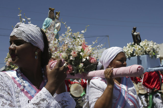 In this October 9, 2016 photo, women carry statues of Our Lady of the Rosary and St. Benedict during the annual Afro-Christian Congada celebration in Catalao, Goias state, Brazil. Our Lady of the Rosary represents the African divinity Yemanja, or Sea Mother, and St. Benedict corresponds to the African divinity Ossaim, a god of nature. (Photo by Eraldo Peres/AP Photo)