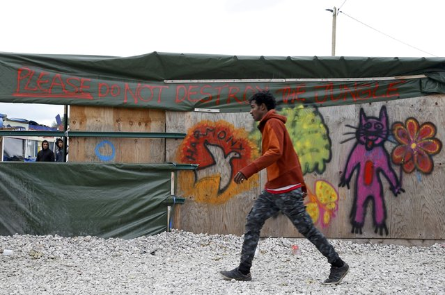 """A migrant walks past a shop with the message """"Please do not destroy the Jungle"""" in what is known as the """"Jungle"""", a sprawling camp in Calais, France, October 12, 2016. The French government will dismantle the filthy, ramshackle camp outside Calais that has become a searing symbol of Europe's struggle to respond to an influx of migrants fleeing war and poverty. (Photo by Pascal Rossignol/Reuters)"""