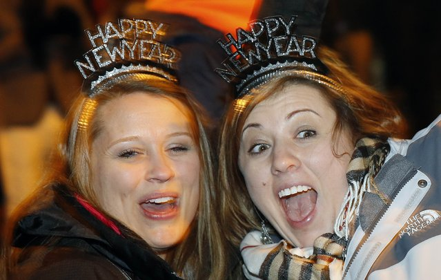 Revellers from North Carolina, U.S. cheer as they wait for fireworks to start at the London Eye on the River Thames during New Year celebrations in London December 31, 2014. (Photo by Suzanne Plunkett/Reuters)