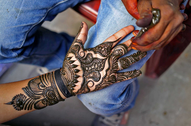 An artist applies henna on a woman's hand ahead of the Hindu festival of Karva Chauth in Jammu October 17, 2016. (Photo by Mukesh Gupta/Reuters)