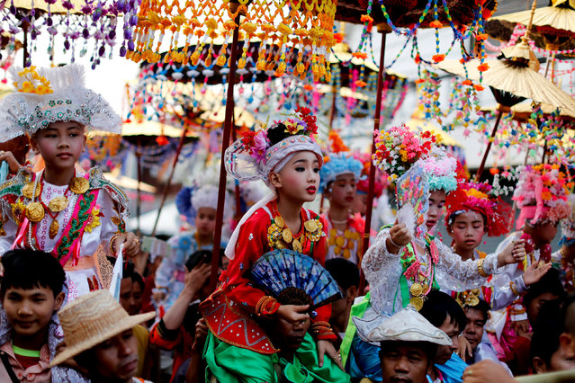 Children are carried on shoulders during an annual Poy Sang Long procession, a traditional rite of passage for boys to be initiated as Buddhist novices, in Mae Hong Son, Thailand, April 3, 2018. (Photo by Jorge Silva/Reuters)