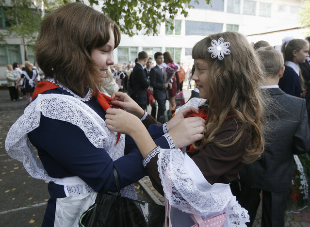 School children, wearing red neckerchiefs, a symbol of the Young Pioneer Organisation, prepare before a ceremony to mark the beginning of a new academic year at school-liceum number 12 in Russia's Siberian city of Krasnoyarsk, September 1, 2012. (Photo by Ilya Naymushin/Reuters)
