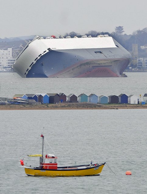 "The stricken vessel ""Hoegh Osaka"" lies trapped on her side on the Brambles Sand Bank between Calshot Bay and Cowes on The Isle of Wight, Britain, 05 January 2015. A high tide on 04 January was not enough to shift the fully loaded car transporter that was deliberately run aground when it developed a list shortly after leaving the south of England port of Southampton. (Photo by Gerry Penny/EPA)"