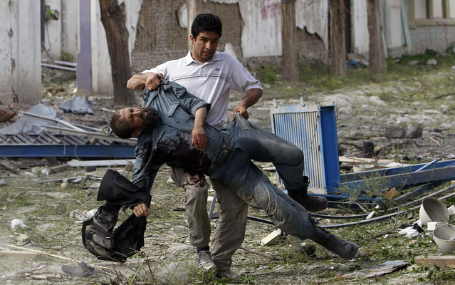 A wounded Afghan policeman is carried away from the site of an explosion in Kabul May 24, 2013. Several large explosions rocked a busy area in the centre of the Afghan capital, Kabul, on Friday with Reuters witnesses describing shooting in the area. (Photo by Omar Sobhani/Reuters)