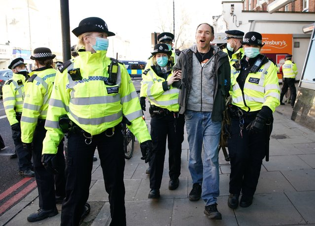 Police detain a man during an anti-lockdown protest in Clapham Common, London, United Kingdom on January 9, 2021. Rabbles gathered in London despite the plea of experts and authorities to stay at home to stop the spread of the deadly bug as cases continue to soar. (Photo by Aaron Chown/PA Images via Getty Images)