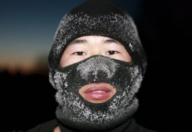 A new recruit People's Liberation Army (PLA) soldier poses for photographs during a training session in cold winter temperatures at a military base in Heihe, Heilongjiang province, China, November 29, 2015. (Photo by Reuters/China Daily)