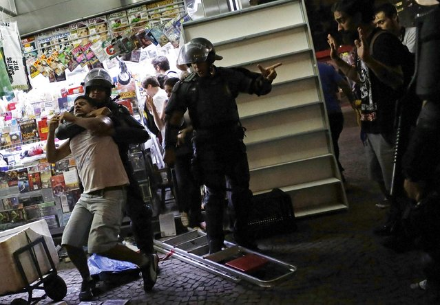 Riot police detain a demonstrator during a protest against fare hikes for city buses, subway and trains in Sao Paulo January 16, 2015. (Photo by Nacho Doce/Reuters)