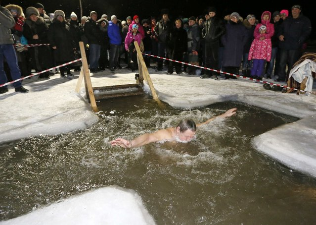 A man immerses himself in an ice hole in the Chulym river, with the air temperature at about minus 12 degrees Celsius (10.4 degrees Fahrenheit), during celebrations for Russian Orthodox Epiphany outside of the town of Nazarovo, Krasnoyarsk region January 19, 2015. (Photo by Ilya Naymushin/Reuters)