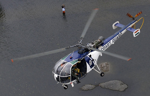 A flood-affected man waves to a coastguard chopper in Chennai, India, Saturday, December 5, 2015. Although floodwaters have begun to recede, vast swaths of Chennai and neighboring districts were still under 2 1/2 to 3 meters (8 to 10 feet) of water, with tens of thousands of people in state-run relief camps. (Photo by Arun Sankar K./AP Photo)