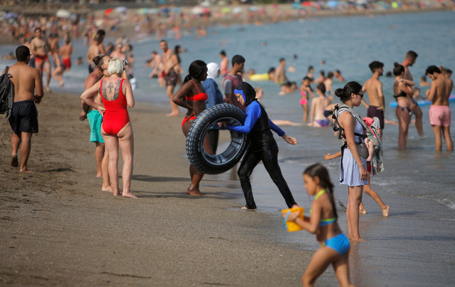 Tourists cool off on La Malagueta beach on a hot summer day during the first weekend of the summer in Malaga, southern Spain, June 24, 2018. (Photo by Jon Nazca/Reuters)