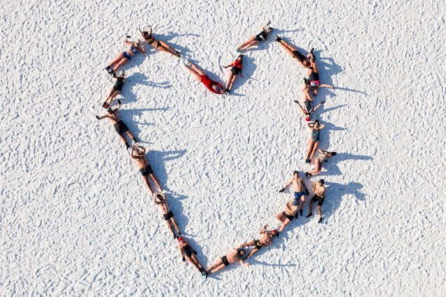 Lovers of winter swimming draw a heart as they pose lying on the icy beach after swimming in the icy water of the Baltic sea in Gdansk, Poland on February 14, 2021, on the occasion of the Valentine's day. (Photo by Mateusz Slodkowski/AFP Photo)
