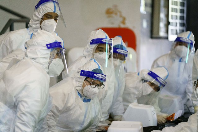 Medical worker wearing personal protective equipment (PPE) listen to briefing at a COVID-19 testing center in Shah Alam city, Selangor states, Malaysia, Wednesday, February 17, 2021. The second movement control order (MCO) currently enforced across the country, has been extended to March. 4 in some of the states, to try to halt the spread of the coronavirus. (Photo by Vincent Thian/AP Photo)