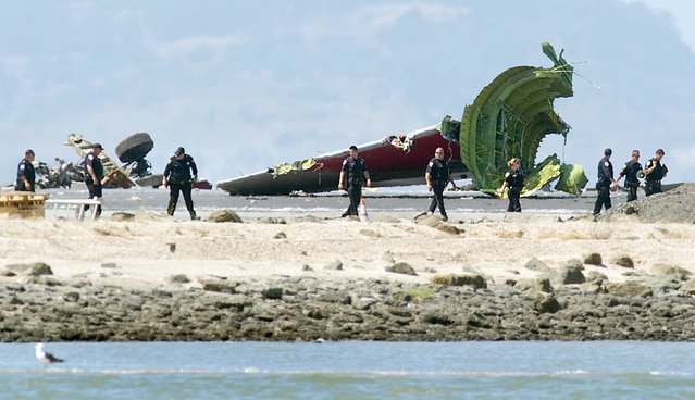 Investigators pass the detached tail and landing gear of Asiana Flight 214 after it crashed at San Francisco International Airport on Saturday, July 6, 2013, in San Francisco. (Photo by Noah Berger/AP Photo)