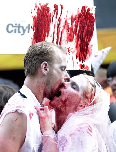 A couple dressed up as zombies takes part in a zombie walk in the Gaslamp Quarter during the Comic Con International convention in San Diego, California July 13, 2012. (Photo by Mario Anzuoni/Reuters)
