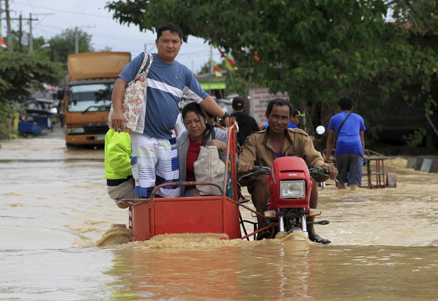 Residents ride on motorcycle taxi to cross a flooded road after heavy rain at Candaba town, Pampanga province, north of Manila, December 17, 2015. Nine people were killed and hundreds spent the night huddled on their roofs in the central Philippines as floods generated by a powerful typhoon inundated villages, disaster officials said on Wednesday. (Photo by Romeo Ranoco/Reuters)
