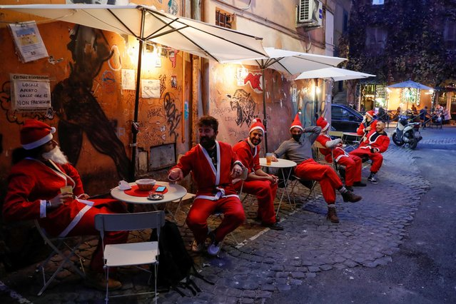 Men dressed in Santa suits sit in outdoor tables in Trastevere one day before Italy goes back to a complete lockdown as part of efforts put in place to curb the spread of the coronavirus disease (COVID-19), in Rome, Italy, December 23, 2020. (Photo by Remo Casilli/Reuters)