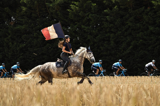 A spectator on horseback waves a French flag as the pask rides during the eighth stage of the 105 th edition of the Tour de France cycling race between Dreux and Amiens, northern France, on July 14, 2018. (Photo by Marco Bertorello/AFP Photo)