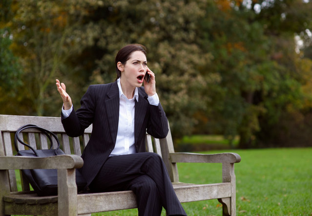 Business woman on park bench using mobile phone. (Photo by Dougal Waters/Getty Images)