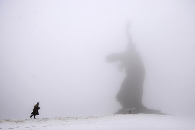 A man dressed in Red Army World War II uniform walks toward the monument to Motherland during ceremonies marking the 72nd anniversary of the Battle of Stalingrad in the southern Russian city of Volgograd, once known as Stalingrad, Monday, February 2, 2015. The city, which was known as Stalingrad during World War II, suffered six months of intensive fighting that ended with the Red Army's defeat of the Nazis, which marked a decisive turn in World War II. (Photo by Dmitry Rogulin/AP Photo)