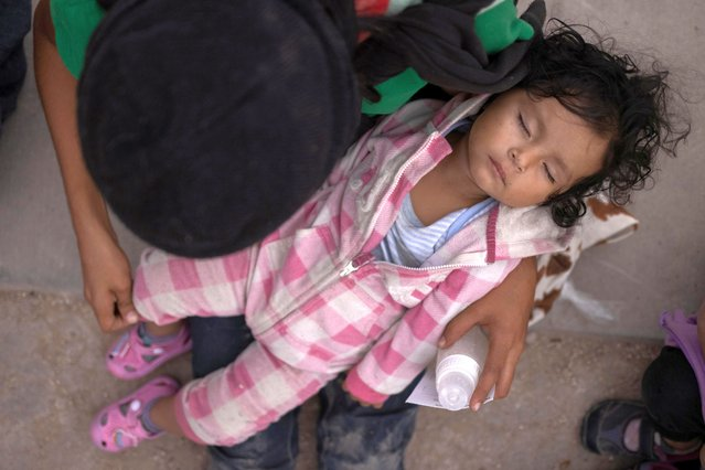 Cherie, a one-year-old old asylum-seeking migrant girl from Honduras, sleeps in her mother's arm after they crossed the Rio Grande river into the United States from Mexico on a raft in Penitas, Texas, U.S., March 16, 2021. (Photo by Adrees Latif/Reuters)