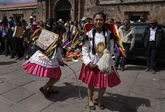 "In this Sunday, August 5, 2018 photo, a dancer winces in pain as she is whipped by a fellow dancer in an adaptation of the Inca warrior dance known as ""Kachampa"", during celebrations honoring Our Lady of Copacabana, in Cuzco, Peru. (Photo by Martin Mejia/AP Photo)"