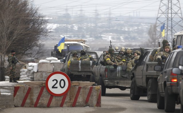 Ukrainian government troops sit in the back of pick-up trucks as they pass a checkpoint near the town of Mariupol, Ukraine, Tuesday, February 10, 2015. The intense fighting, which the U.N. says has killed more than 5,300 people since April, comes ahead of a crucial summit including Western leaders on Wednesday as well as peace talks later Tuesday. (Photo by Petr David Josek/AP Photo)