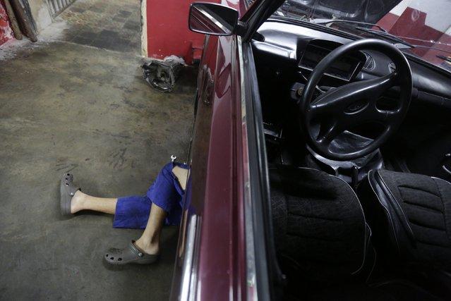 A mechanic works on a Lada at a car workshop in Havana February 9, 2015. (Photo by Enrique De La Osa/Reuters)