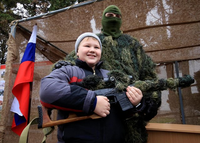 A boy and a serviceman pose for a picture during Marines Day celebration in the Black Sea port of Sevastopol, Crimea, November 27, 2016. (Photo by Pavel Rebrov/Reuters)