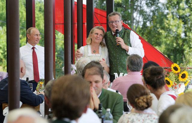Austria's Foreign Minister Karin Kneissl is embraced by her groom Wolfgang Meilinger during their wedding celebrations as Russia's President Vladimir Putin looks on in Gamlitz, Austria on August 18, 2018. (Photo by Alexei Druzhinin/Sputnik/Kremlin via Reuters)