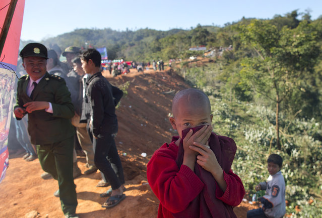 In this January 12, 2015 photo, a novice Buddhist monk covers his nose and mouth with his robe to protect himself from the smoke of burning narcotics during a ceremony in Mar Wong Village, northern Shan state, Myanmar, held by Ta'ang rebels. (Photo by Gemunu Amarasinghe/AP Photo)