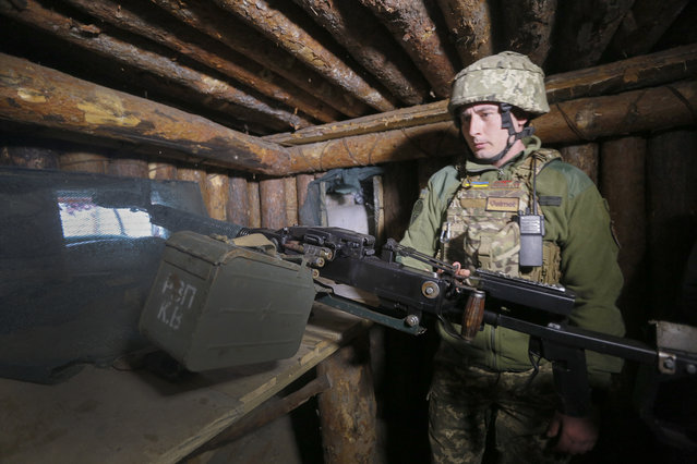 A Ukrainian soldier is seen at fighting positions on the line of separation from pro-Russian rebels near Luhansk, Ukraine, Friday, April 16, 2021. Growing cease-fire violations and a massive Russian military buildup are causing tensions to rise in the conflict in eastern Ukraine, where more than 14,000 people have died in seven years of fighting between forces from Kyiv and separatists loyal to Moscow. (Photo by Efrem Lukatsky/AP Photo)