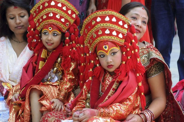 Nepalese girls wearing traditional attires attend the Kumari Puja, a mass worship, at Hanuman Dhoka in Durbar Square in Kathmandu, September 17, 2013. (Photo by Bikash Dware/Reuters)