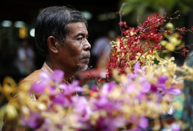 A man sells flowers at a market near Petak Sembilan Chinese Buddhist temple on the eve of Chinese Lunar New Year celebrations, at Petak Sembilan temple in Jakarta, February 18, 2015. (Photo by Darren Whiteside/Reuters)