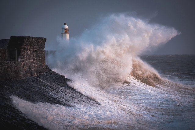 Waves crash over the lighthouse at Porthcawl, South Wales, Britain on August 22, 2020. (Photo by South West News Service)